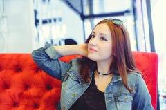 Une jeune femme arabe d'aspect sur un sofa rouge dans un café piaulant Images stock