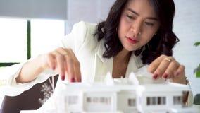 Une jeune femme architecte asiatique en train de construire une maison modèle banque de vidéos