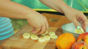Une jeune femme arrange des morceaux avec une banane dans une cuvette avec la salade de fruits pour un pique-nique banque de vidéos
