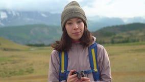 Une jeune femme asiatique avec un sac à dos regarde l'appareil-photo avant de s'élever Montagnes brumeuses à l'arrière-plan clips vidéos