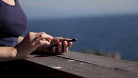 Une jeune femme attirante à l'aide d'un smartphone au balcon d'un hôtel de station thermale, une femme photographie un coucher du banque de vidéos
