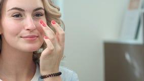 Une jeune femme attirante à un salon vérifiant ses cheveux dans le miroir Image libre de droits
