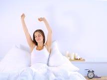 Une jeune femme attirante s'étirant dans le lit après s'être réveillé Image stock