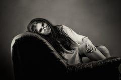 Une jeune femme attirante se trouve sur un sofa en cuir image libre de droits