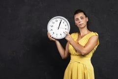 Une jeune femme attirante tient une horloge ronde dans des ses mains Le concept du temps La fille observe le temps photo libre de droits