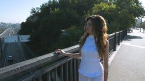 Une jeune femme avec de longs cheveux marche le long du pont piétonnier Elle regarde les voitures qui conduisent en bas clips vidéos