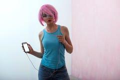 Une jeune femme avec des cheveux roses et des verres de néon utilise un smartphone photos stock