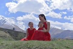 Une jeune femme avec deux filles dans des robes rouges se reposant dans les montagnes couronn?es de neige au printemps photos stock