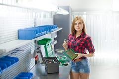 Une jeune femme avec le plat électronique dans un garage Photographie stock libre de droits