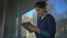 Une jeune femme avec un comprimé à la fenêtre de la Chambre, 4k banque de vidéos