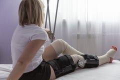 Une jeune femme avec un orthosis sur sa jambe s'assied sur le lit Essaye de se lever avec des b?quilles P?riode postop?ratoire image libre de droits