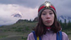 Une jeune femme avec un sac à dos et un phare regarde l'appareil-photo avant de s'élever Montagnes brumeuses à l'arrière-plan clips vidéos