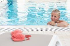 Une jeune femme blonde dans une piscine avec le bikini rouge est partie par la piscine Photos libres de droits