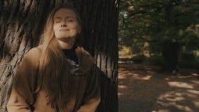 Une jeune femme blonde se tenant sous un arbre dans la forêt d'automne banque de vidéos