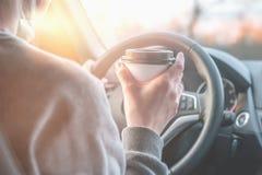 Une jeune femme boit du café tout en conduisant une voiture tout en voyageant Le concept de la sécurité routière images stock