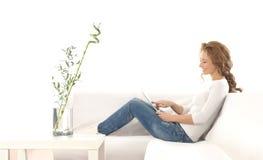 Une jeune femme caucasienne détendant sur un sofa photographie stock
