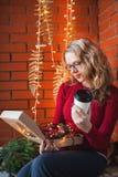 Une jeune femme décore une maison pendant Noël et la nouvelle année Tient une boîte de jouets dans la perspective d'un mur de bri Photo libre de droits