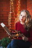 Une jeune femme décore une maison pendant Noël et la nouvelle année Tient une boîte de jouets dans la perspective d'un mur de bri Photos libres de droits