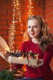 Une jeune femme décore une maison pendant Noël et la nouvelle année Tient une boîte de jouets dans la perspective d'un mur de bri Images libres de droits