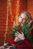 Une jeune femme décore une maison pendant Noël et une nouvelle année Photo libre de droits