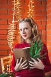 Une jeune femme décore une maison pendant Noël et une nouvelle année Tient une branche d'un arbre de Noël Photos stock