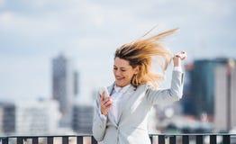 Une jeune femme d'affaires avec le smartphone se tenant sur une terrasse, exprimant l'excitation photos libres de droits