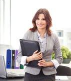 Une jeune femme d'affaires de brunette retenant un dépliant Image stock