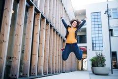 Une jeune femme d'affaires sautant dehors, exprimant l'excitation image libre de droits