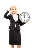 Une jeune femme d'affaires tenant une horloge murale dans sa main et gestu Images stock