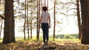 Une jeune femme dans des jeans marche par une forêt à l'arrière-plan d'un coucher du soleil banque de vidéos