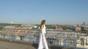 Une jeune femme dans des vêtements blancs, marchant le long de la plate-forme d'observation de touristes Beau panorama de la vill banque de vidéos