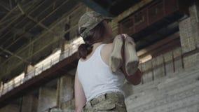 Une jeune femme dans l'uniforme militaire mettant ses chaussures à talons hauts sur son épaule et regardant dans le sourire de ca banque de vidéos