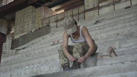 Une jeune femme dans l'uniforme militaire se reposant sur les escaliers concrets froids dans le bâtiment abandonné, laçant vers l clips vidéos