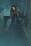 Une jeune femme dans la robe longue noire avec de longs cheveux regardant directement c photos stock