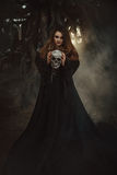 Une jeune femme dans la robe longue noire avec de longs cheveux regardant directement c image libre de droits
