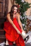Une jeune femme dans la robe rouge d'hiver sur un porche décoré des décorations de Noël, mettant sur des patins et le sourire photos stock
