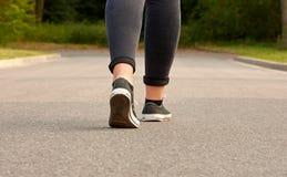 Une jeune femme dans les espadrilles et des jeans marchant sur la route goudronnée Photo libre de droits