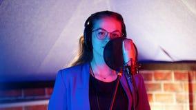 Une jeune femme dans les verres et des écouteurs chantant dans le studio Regard dans l'appareil-photo banque de vidéos