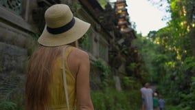 Une jeune femme dans une robe jaune marchant au passage couvert de promenade ou de peintre d'arête de Campuhan dans Ubud Destinat banque de vidéos