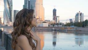 Une jeune femme dans un costume blanc se tient sur le remblai de ville banque de vidéos