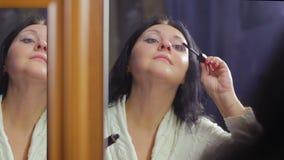 Une jeune femme dans un manteau blanc devant un miroir applique le mascara sur ses cils clips vidéos