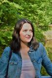 Une jeune femme dans une veste de denim se tient en parc et regarde au côté photographie stock libre de droits