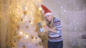 Une jeune femme danse tout en tenant un cadeau de Noël banque de vidéos