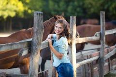 Une jeune femme de sourire avec les cheveux bouclés s'est habillée dans des jeans à l'écurie avec des chevaux image stock