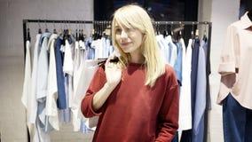 Une jeune femme de sourire heureuse blonde a juste acheté des vêtements dans une boutique image libre de droits