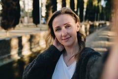 Une jeune femme de sourire se tient en parc et fait un selfie La fille prend des photos d'elle-même Portrait femelle photographie stock