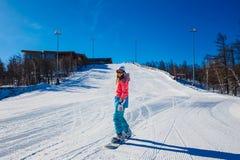 Une jeune femme descend des montagnes sur un surf des neiges photos stock
