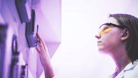 Une jeune femme en verres jaunes appuie sur un bouton sur l'équipement photo stock