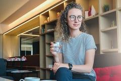 Une jeune femme en verres s'assied sur un sofa dans le lobby, le restaurant et les prises d'hôtel par verre de l'eau, tandis que  Photos libres de droits
