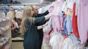 Une jeune femme enceinte heureuse choisit des vêtements pour un nouveau-né dans un magasin du ` s d'enfants clips vidéos
